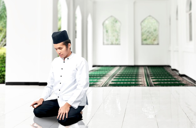 Asian muslim man in praying position (salat) on the mosque