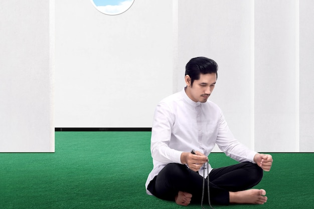 Asian muslim man praying with prayer beads on his hands on the mosque