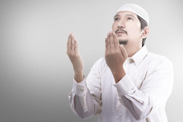 霧の背景を持つ彼の手に数珠で祈るアジアのイスラム教徒の男性
