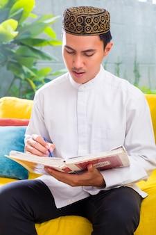 Asian muslim man reading koran or quran