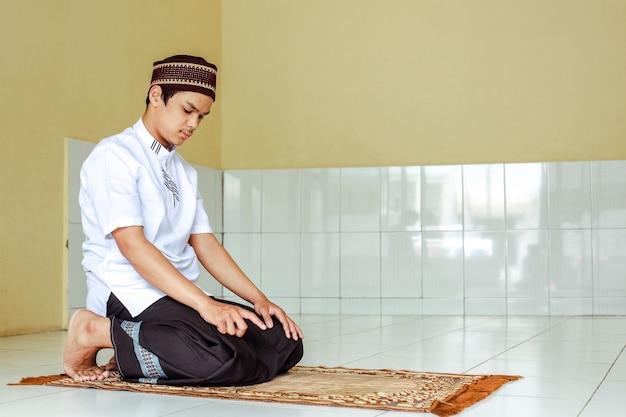 Asian muslim man salat on the prayer mat with early tahiyat posing
