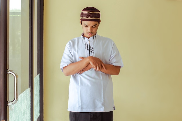 Asian muslim man salat with hand in chest inside the mosque