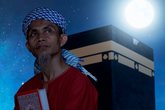 Asian muslim man sitting and holding quran with kaaba view and night scene background
