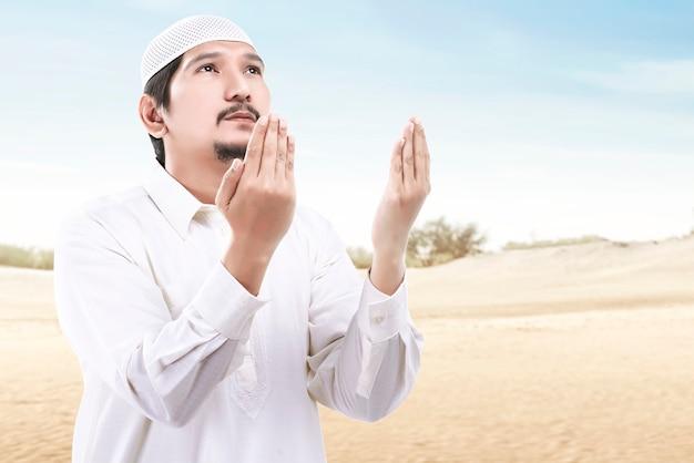 手を上げて立って、青い空を背景に祈るアジアのイスラム教徒の男性