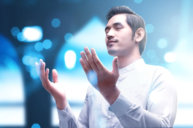 手を上げて立って、ぼやけた明るい背景で祈っているアジアのイスラム教徒の男性