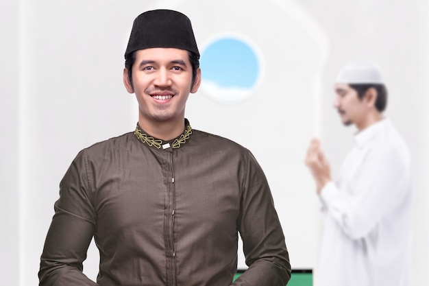 Asian muslim man standing while raised hands and praying on the mosque