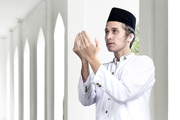 Asian muslim man standing while raised hands and praying