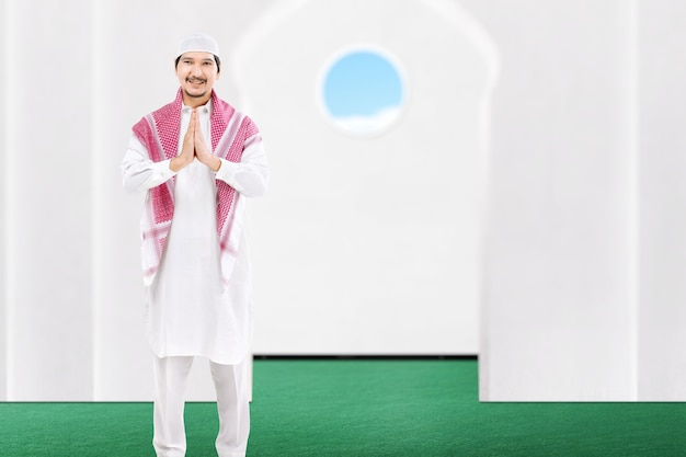 Asian muslim man standing with greeting gesture on the mosque