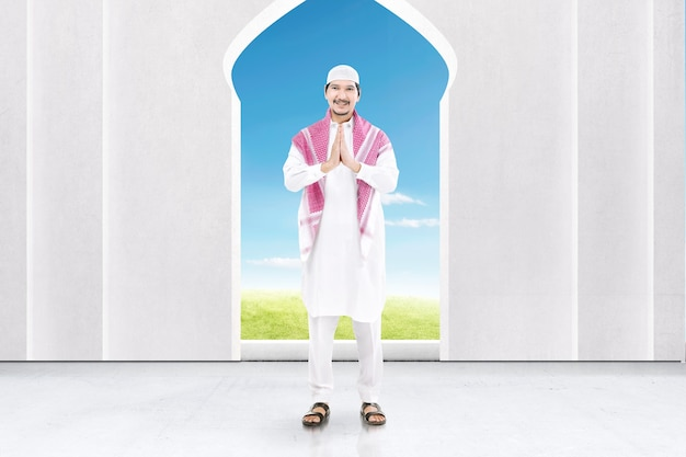 모스크에 인사 제스처와 함께 서 아시아 무슬림 남자
