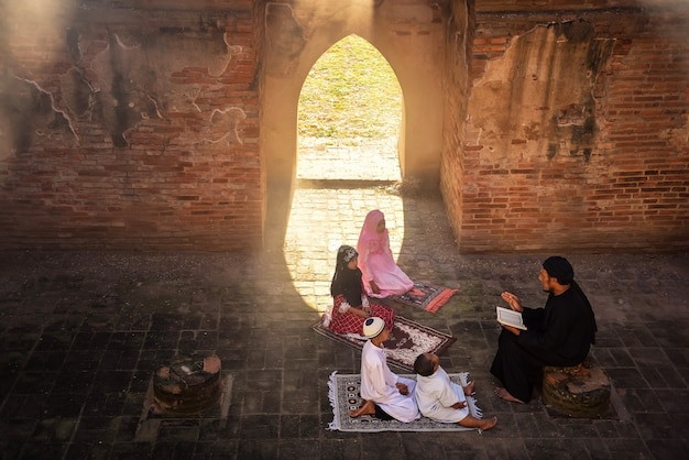 An asian muslim man taught his son and young daughter to read prayers to god in a mosque with sunlight shining through windows and doors.