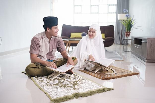 Азиатский мужчина-мусульманин учит женщину чтению корана или корана в гостиной мусульманская пара молится дома
