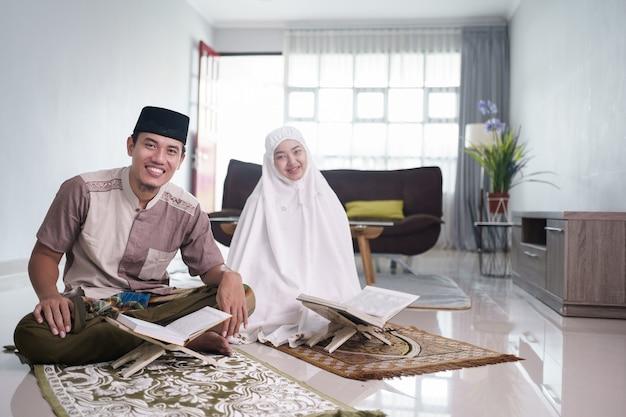 Asian muslim man teaching woman reading koran or quran in living room muslim couple praying at home