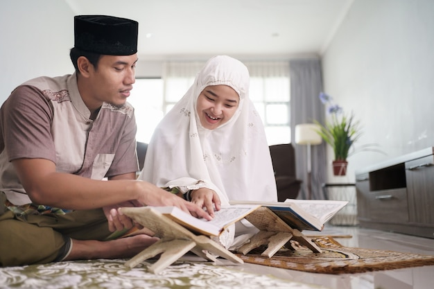 Asian muslim man teaching woman reading koran or quran in living room muslim couple praying at home