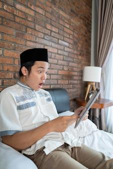 태블릿을 사용하고 놀란 아시아 무슬림 남자