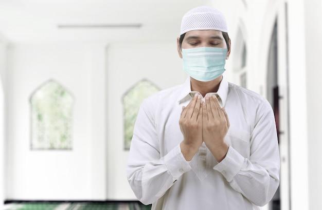 Asian muslim man wearing flu mask standing while raised hands and praying