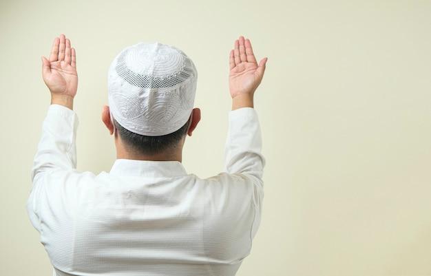 옆에 빈 공간으로 기도하는 마스크를 쓴 아시아 이슬람 남자