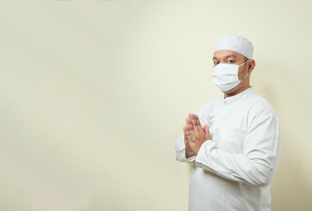 ゲストへの挨拶のジェスチャーでマスクを身に着けているアジアのイスラム教徒の男性
