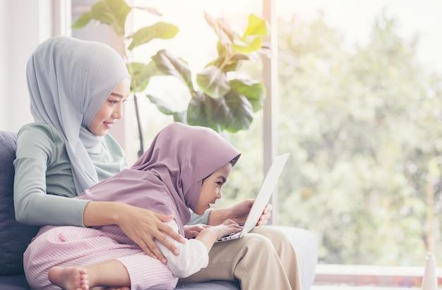 一緒にラップトップを使用すると笑顔のアジアのイスラム教徒の母と娘