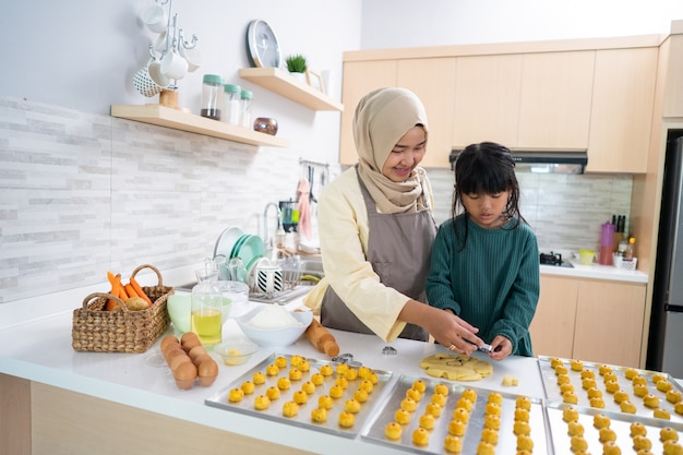 Asian muslim mother during ramadan activity with her daughter making a nastar cake together at home in the kitchen for celebrating eid mubarak kareem