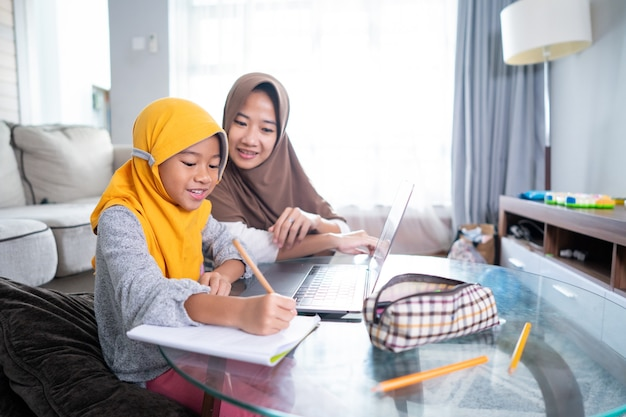 Asian muslim mother help her daughter to learn online using laptop studying from home