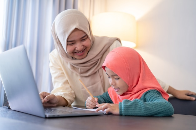 Asian muslim mother help her daughter to study during home schooling in the evening