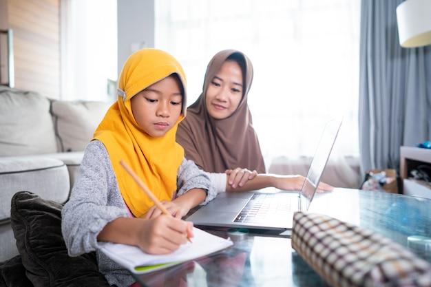 アジアのイスラム教徒の母親は、娘が自宅から勉強しているラップトップを使用してオンラインで学ぶのを助けます