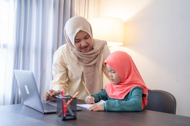 アジアのイスラム教徒の母親は、娘が夕方のホームスクーリング中に勉強するのを手伝っています