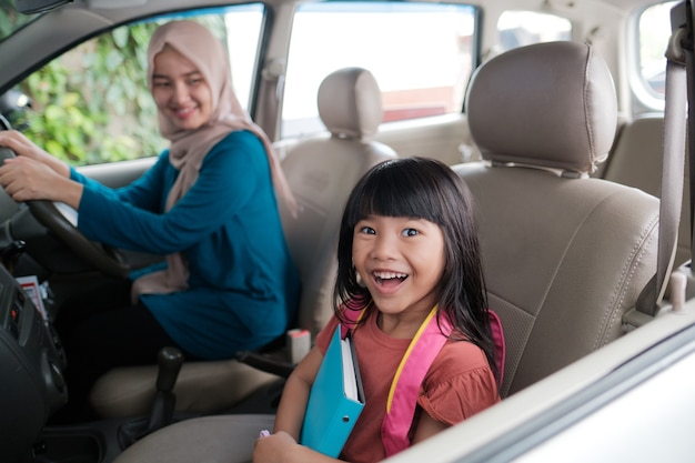 Asian muslim mother taking her daughter to school in the morning. happy student going back to school