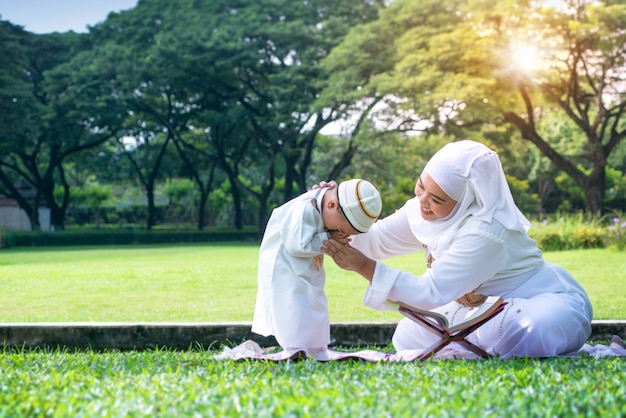 Asian muslim mother teaching his little son to pray to god with rosary at park