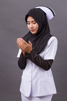 Asian muslim nurse praying, prayer hand gesture