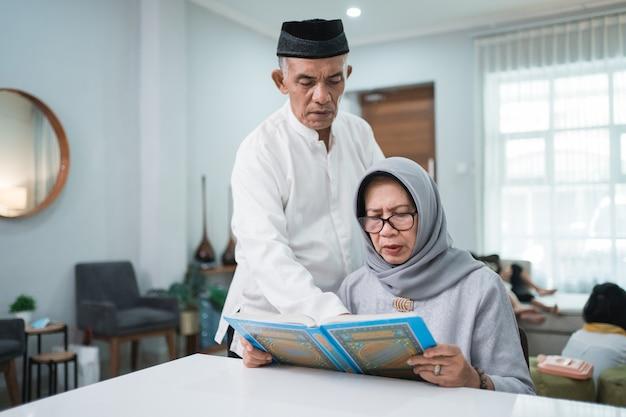 Азиатский мусульманский старший мужчина учит жену читать коран или коран в гостиной. мусульманская пара молится дома