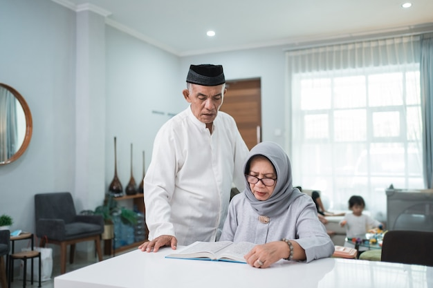 Asian muslim senior man teaching wife reading koran or quran in living room. muslim couple praying at home