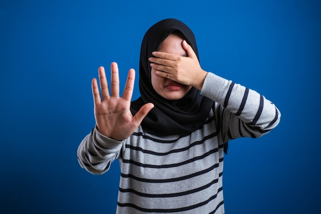 Asian muslim student girl making stop gesture, against blue background. stop to do bullying to her