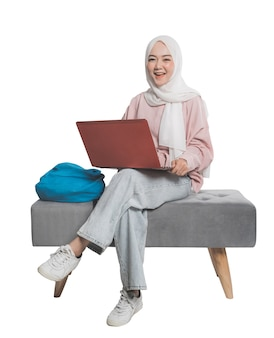 Asian muslim student holding laptop in front of white isolated background