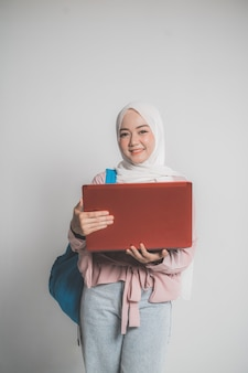 격리 된 흰색 배경 앞에서 노트북을 들고 아시아 이슬람 학생