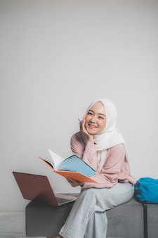 白い孤立した背景の前にラップトップを保持しているアジアのイスラム教徒の学生