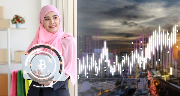 Asian muslim trader or businesswoman looking virtual hologram price graph and indicator candlestick chart stock trading with laptop computer and city background. investing on stock concept.