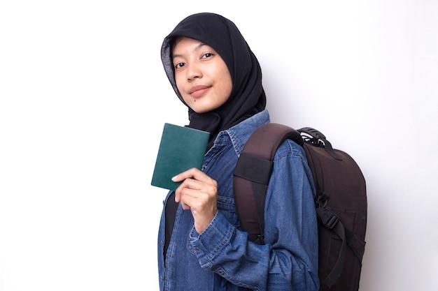 ホワイトスペースにパスポートを保持しているアジアのイスラム教徒の女性バックパッカー