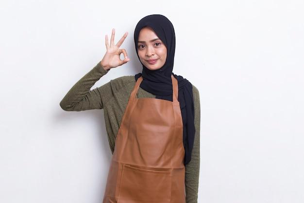 아시아 이슬람 여성 바리스타 웨이트리스가 앞치마를 입고 확인 표시 제스처가 흰색으로 격리되어 있습니다.