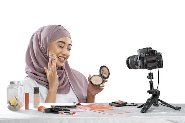 頬にパフパウダーメイクをするアジアのイスラム教徒の女性の美容ブロガーチュートリアル