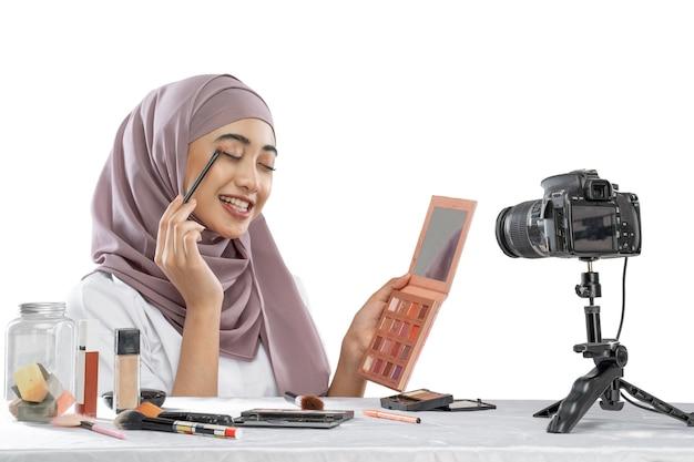 彼女の目にアジアのイスラム教徒の女性の美容ブロガーチュートリアルメイクとビデオを作る
