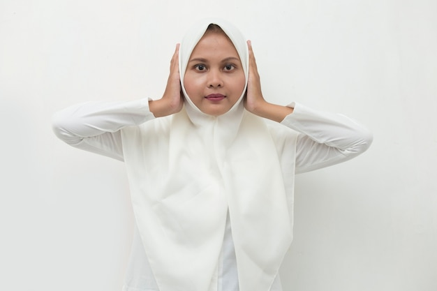 Asian muslim woman covering her ears