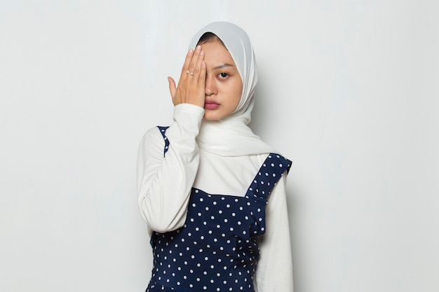 Asian muslim woman covering one eye with hand