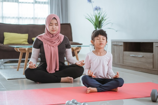 Asian muslim woman and daughter doing yoga exercise and sport at home together in the livingroom