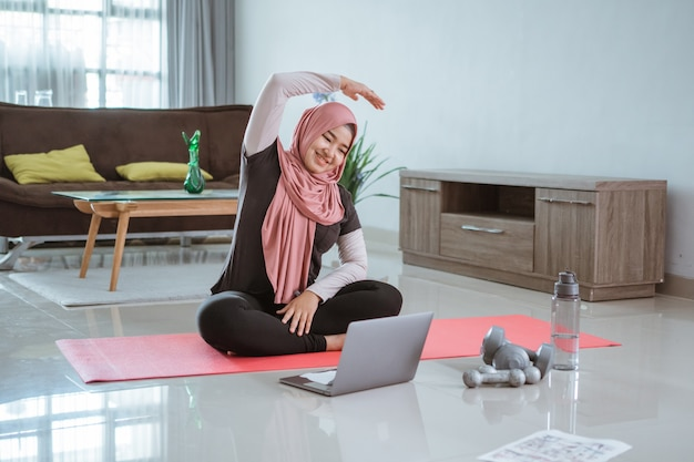 Asian muslim woman doing exercise and sport at home