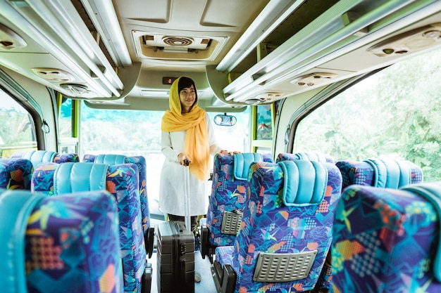 Asian muslim woman doing traveling back to her hometown by riding a bus