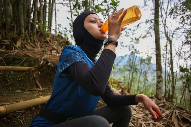 ジョギング、健康、スポーツのコンセプトの後に水を飲むアジアのイスラム教徒の女性。