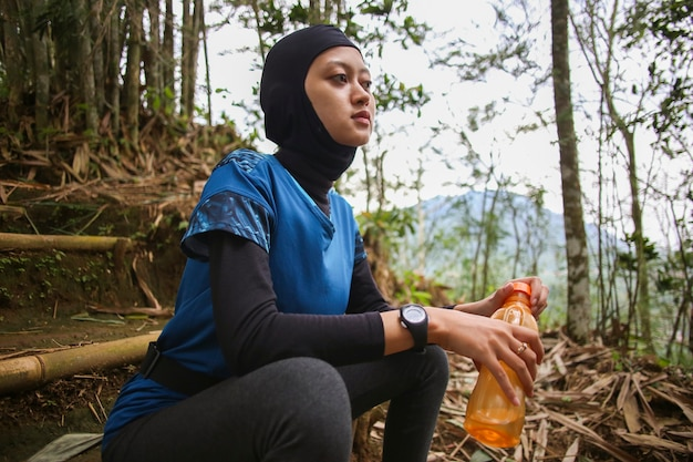 Asian muslim woman drinking water after jogging,healty and sport concept. Premium Photo