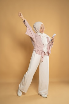 スタジオショットでアジアのイスラム教徒の女性の陶酔感のある腕を上げる