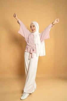 アジアのイスラム教徒の女性の陶酔感のある腕を上げる